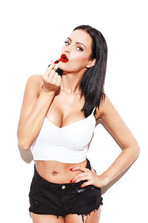 tetas: Mujer atractiva con grandes tetas aplicar lápiz labial rojo, aislado en blanco Foto de archivo