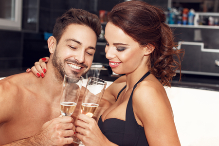 sexy bath: Happy couple with glasses of champagne in jacuzzi, honeymoon