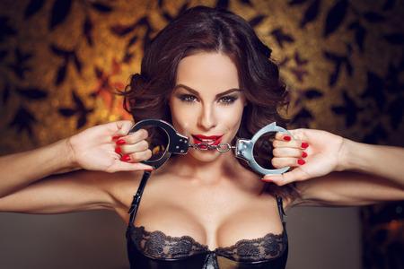 sex: Mujer atractiva la celebración de las esposas en club nocturno, labios rojos, bdsm
