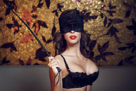 foreplay sex: Sexy woman in lace eye cover holding whip, bdsm