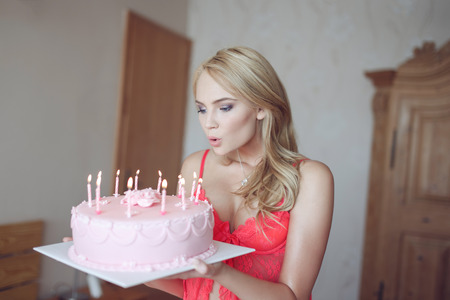 Sexy blonde woman blowing candles on birthday cake at home