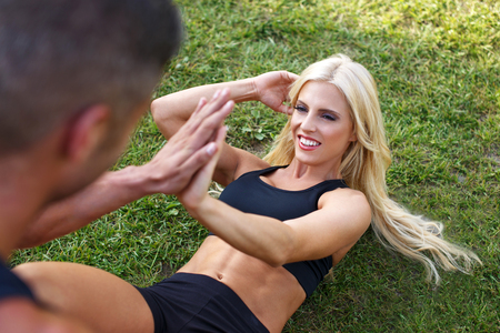 happy young man: Blonde fit woman doing sit ups with man, healthy lifestyle, hi-five