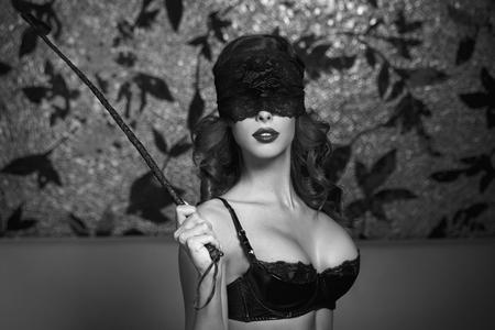 tetas: Mujer atractiva en la cubierta del ojo del cordón que sostiene látigo, blanco y negro, bdsm Foto de archivo