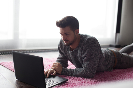 prone: Young man typing on laptop, lie prone on carpet at home Stock Photo
