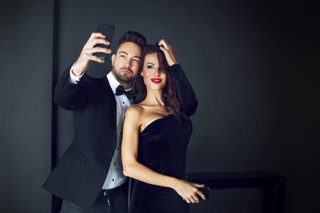 woman red dress: Fashionable rich celebrity couple taking selfie indoor