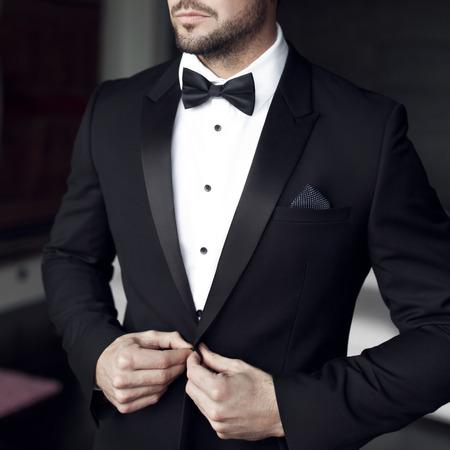 Sexy mężczyzna w smokingu i muszce stwarzających