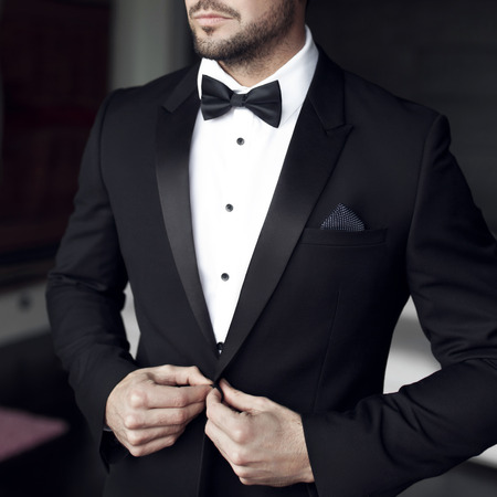 suit tie: Sexy man in tuxedo and bow tie posing