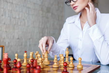 Clever woman moving with queen on chessboard in office, business strategy