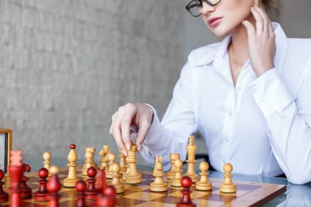fortaleza: mujer inteligente que se mueve con la reina en el tablero de ajedrez en el cargo, la estrategia de negocio