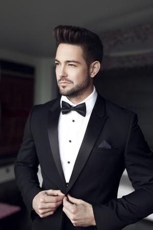 Sexy celebridad de moda del hombre en smoking en interiores
