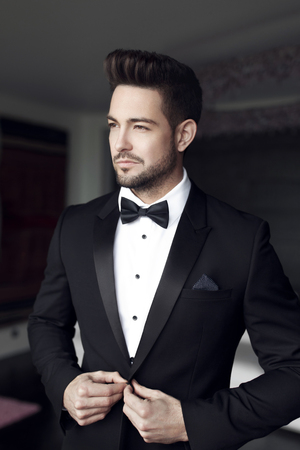 Sexy fashionable man celebrity in tuxedo indoor Stock Photo