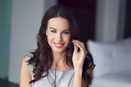 teleconference: Casual brunette woman with headset, customer support from home, online job