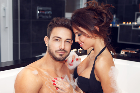 Happy young couple have fun in jacuzzi. Woman washing man, honeymoon