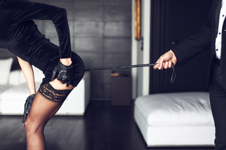 foreplay sex: Sexy rich woman with whip on ass bdsm, closeup