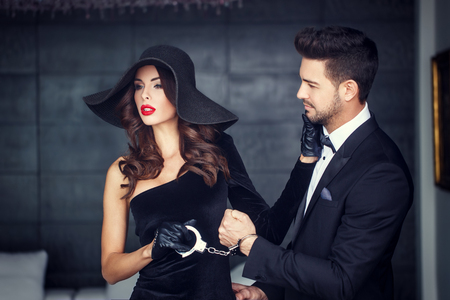 Sexy woman in hat holding young rich lover on handcuffs Stock Photo