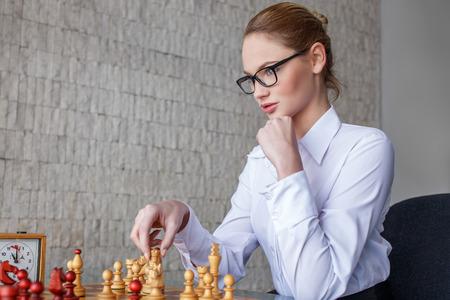 jugando ajedrez: Empresaria joven jugando al ajedrez en la oficina, la competencia