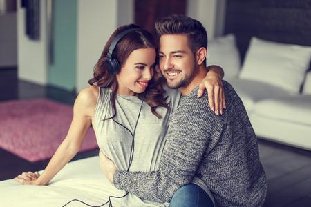 oir: joven pareja feliz escuchando música en interiores, abrazo entre sí