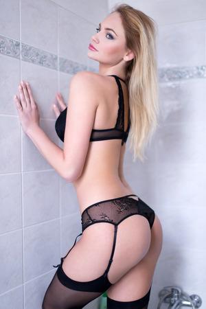 mujer rubia desnuda: La mujer rubia atractiva en el baño posando, ropa interior negro