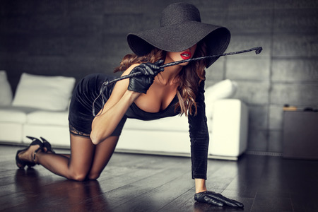 romance sex: Sexy rich woman in hat and whip kneeling on floor indoor