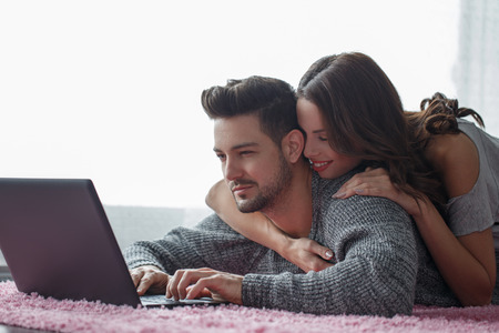 prone: Young couple with tablet lying prone on carpet, wi-fi technology