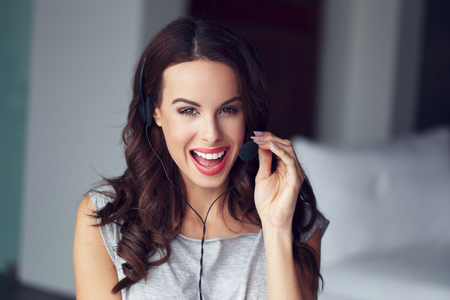 skype: Casual brunette woman with headset, teeth smile, customer support from home, online job Stock Photo