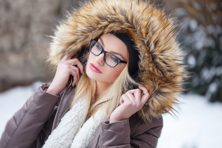 winter fashion: Young blonde woman listening music at winter, outdoor Stock Photo