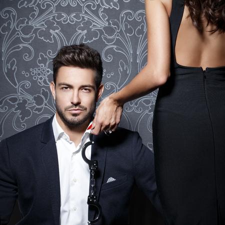 sex: Macho reichen Geschäftsmann mit Liebhaber hält Handschellen an Vintage-Wand Lizenzfreie Bilder