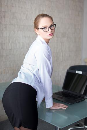 mujer rubia desnuda: Secretaria atractiva en los vidrios que presentan en el escritorio de cristal en la oficina Foto de archivo