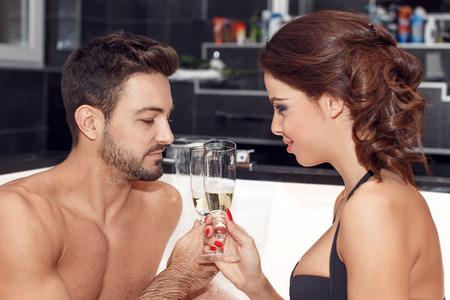 donna innamorata: Felice coppia con bicchieri di champagne nella vasca idromassaggio, luna di miele