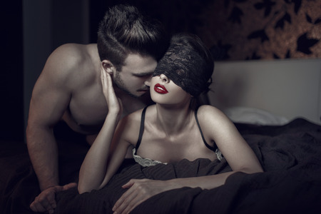 man and woman sex: Sexy woman in lace eye cover and red lips with young lover, foreplay