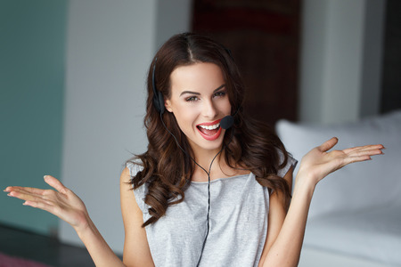 Casual brunette woman with headset, talking, customer support from home, online job Stock Photo