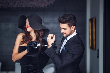 手錠室内帽子保持若い豊かな恋人のセクシーな女性は、歯の笑顔します。 写真素材