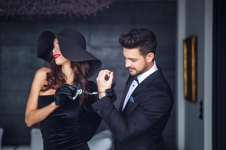 Sexy woman in hat holding young rich lover on handcuffs indoor, teeth smile Standard-Bild