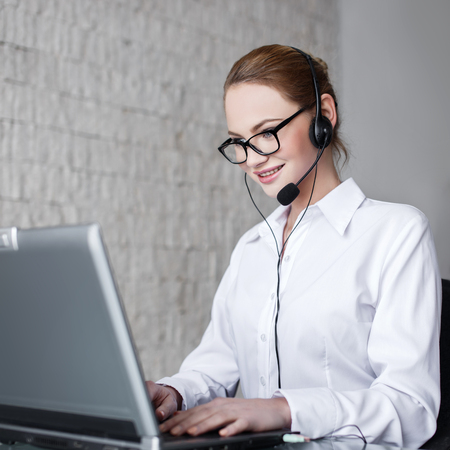 headset woman: Casual customer support worker in office with headset and laptop