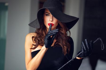 sexuales: mujer dominante atractiva en el sombrero y el látigo que no muestran charla, BDSM