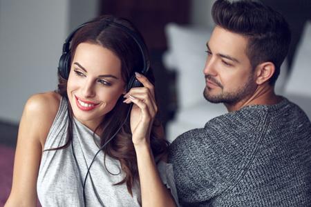 parejas romanticas: feliz pareja de j�venes escuchando m�sica cubierta, sonrisa de los dientes