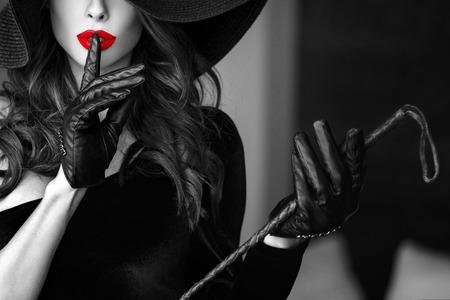 sex: Sexy dominante Frau in Hut und Peitsche keine Rede Nahaufnahme zeigt, bdsm. Selektive Schwarz-Weiß-Färbung.