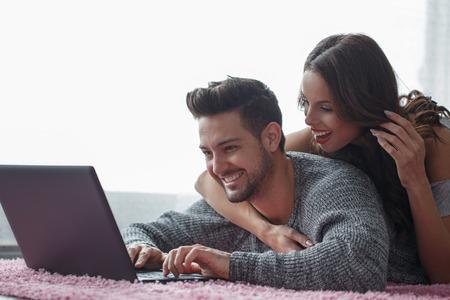 Happy couple prone on carpet online shopping indoor Stock Photo