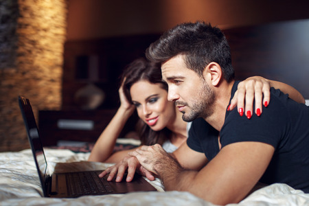 prone: Couple prone on bed with laptop, casual man and woman online shopping. Worry about price