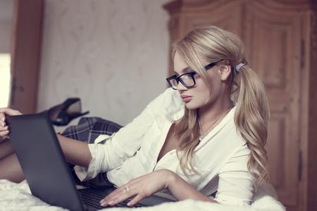 junge nackte mädchen: Sexy blonde Frau in den Gläsern auf dem Bett mit Laptop, online zu flirten.