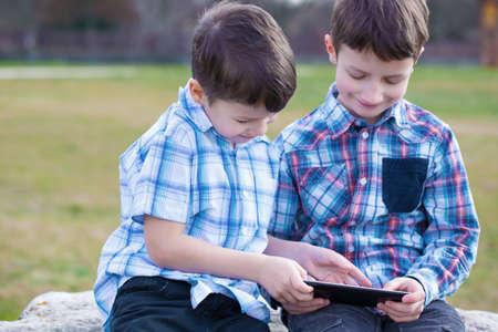 hermanos jugando: Peque�os j�venes hermanos cauc�sicos que juegan en la tableta en la naturaleza