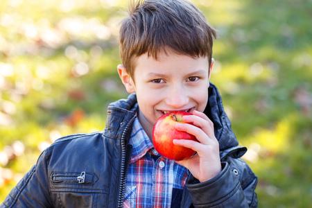 schoolboy: Little schoolboy bite fresh red apple outdoor Stock Photo