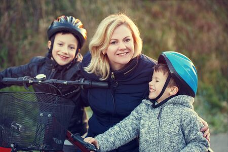 teach: Mother teaching sons cycling, outdoor activity