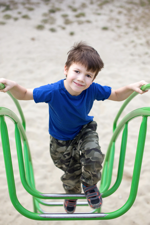jungle gym: Little boy climbing on jungle gym, outdoor Stock Photo