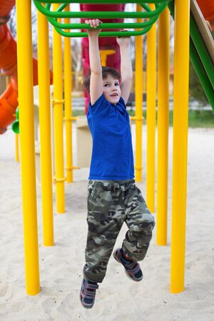 jungle gym: Little boy hanging on jungle gym in park, outdoor