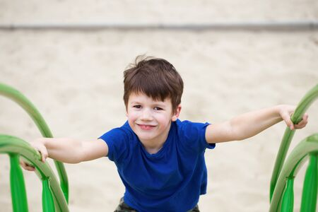 jungle gym: Boy climbing on jungle gym in park, outdoor Stock Photo