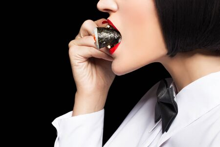 woman eat: Woman eating sushi closeup, side view, isolated on black Stock Photo