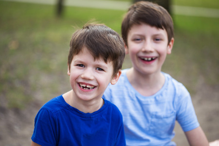 brothers: Happy little caucasian boys laughing in park