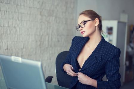 Sexy secretaresse in glazen uitkleden in het kantoor, online flirten en verlangen