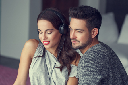 young happy couple: Happy young caucasian couple listening music at home